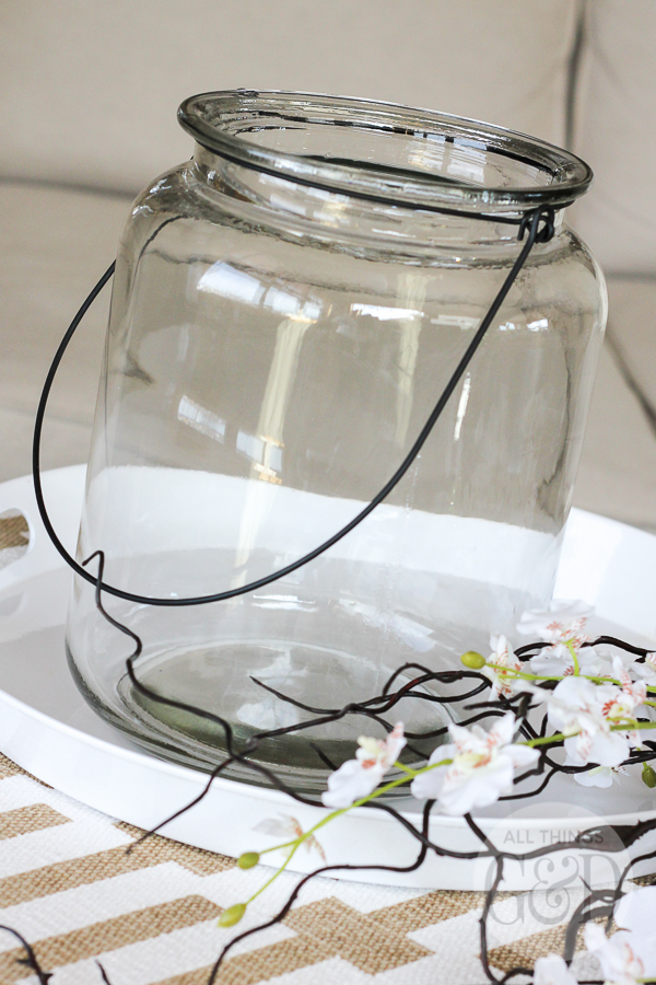 An easy spring floral arrangement using a large glass lantern, long sticks of faux curly willow and floral stems - so simple anyone can do it! | www.allthingsgd.com