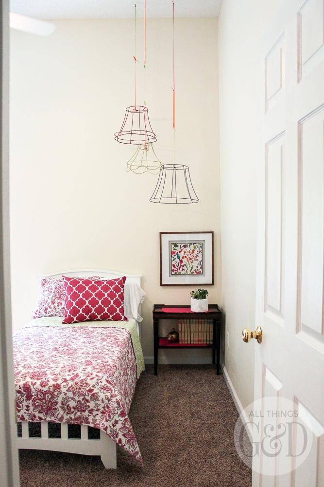 A colorful and playful girl's room created by Dusty Rogers of All Things G&D as part of GMC's 2015 Hidden Treasure Adventure. With a budget of just $285, she furnished and decorated the room with items found along the World's Longest Yard Sale. Wire lamp shades spray painted and hung from the ceiling add pops of color to the corner and accentuate the height of the room's vaulted ceiling. #GMCHTA #HabitatforHumanity