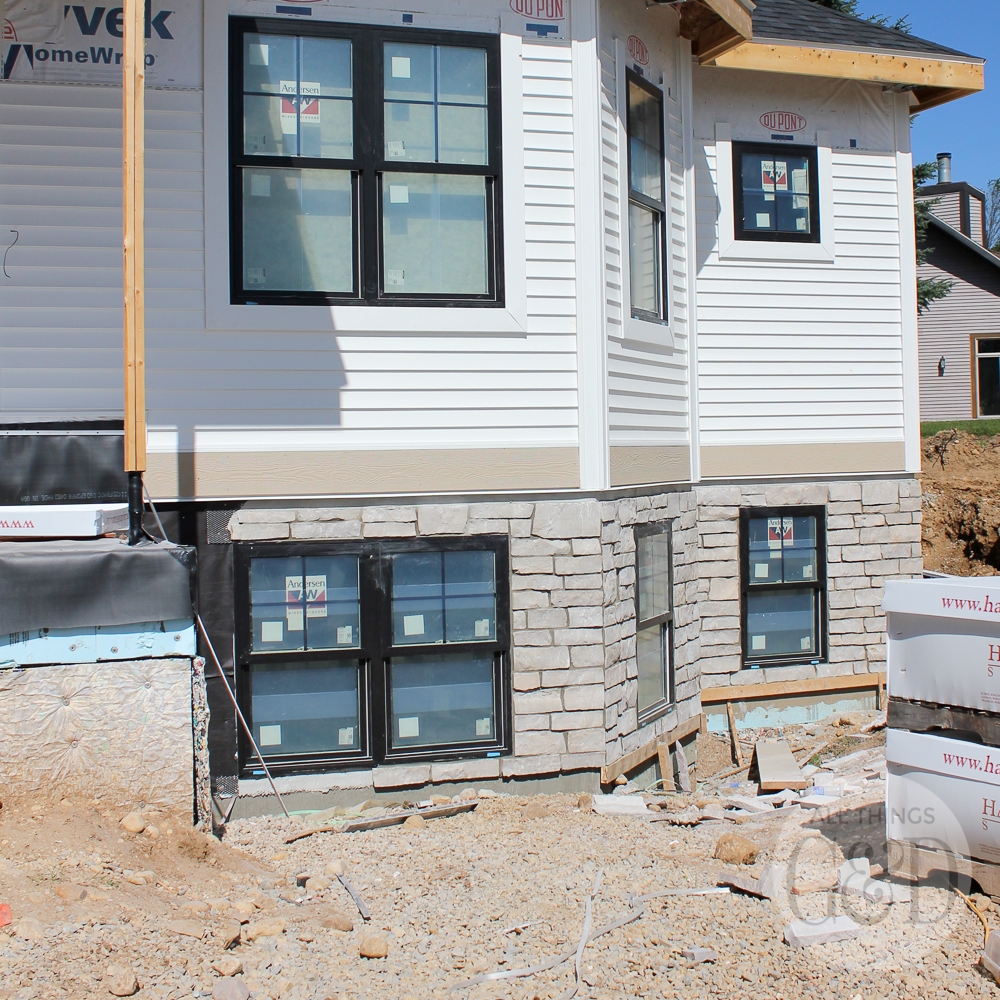 New home construction: white siding and natural stone. | All Things G&D #ATGDdreamhome #newhomeconstruction #customhome #customhomeconstruction #whitesiding #blackwindows #naturalstone #chiltonivory